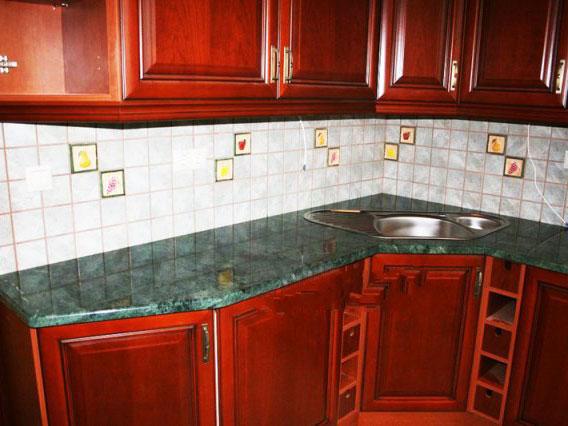 Зелёная столешница из мрамора Verde Guatemala на кухне с красным фасадом