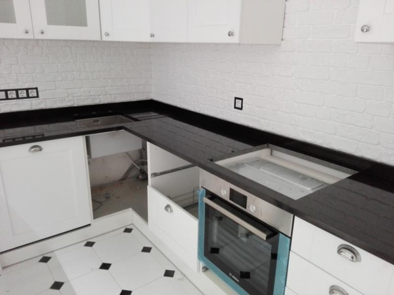 Чёрная столешница из базальта на белом кухонном фасаде