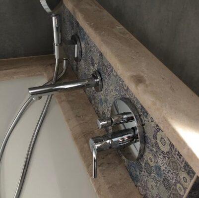 Кран і душ в оточенні мармуру