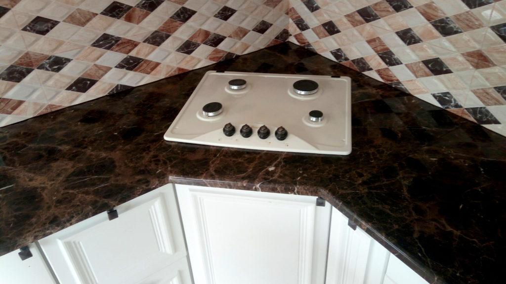 Встроенная в столешницу Emperador Dark белая варочная поверхность, в углу кухни