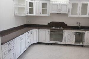 Стільниця з червоного каменю на білій кухні, повний огляд приміщення