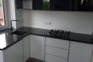 Стільниця з чорного граніту на кухні з білим фасадом